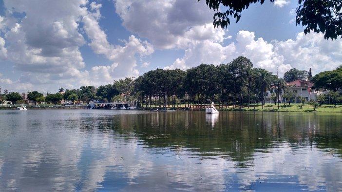 Lago espelhado com pedalinhos em forma de cisnes na margem