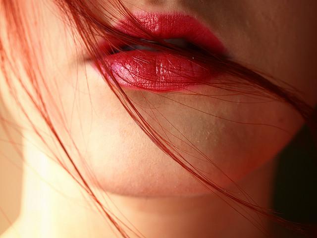 Lábios com batão e cabelo ruivo sobre o rosto